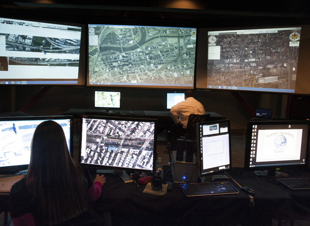 A Persistent Surveillance Systems analyst at the company's command center in Dayton, Ohio, checks over multiscreen video footage of traffic patterns.