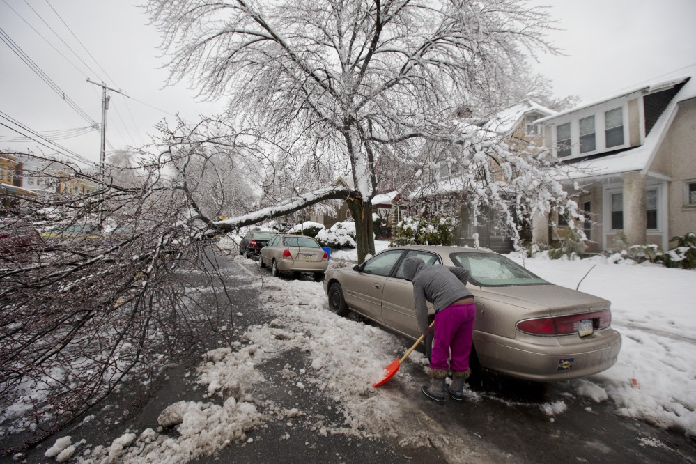 A woman clears snow near a downed tree limb after Wednesday in Philadelphia.
