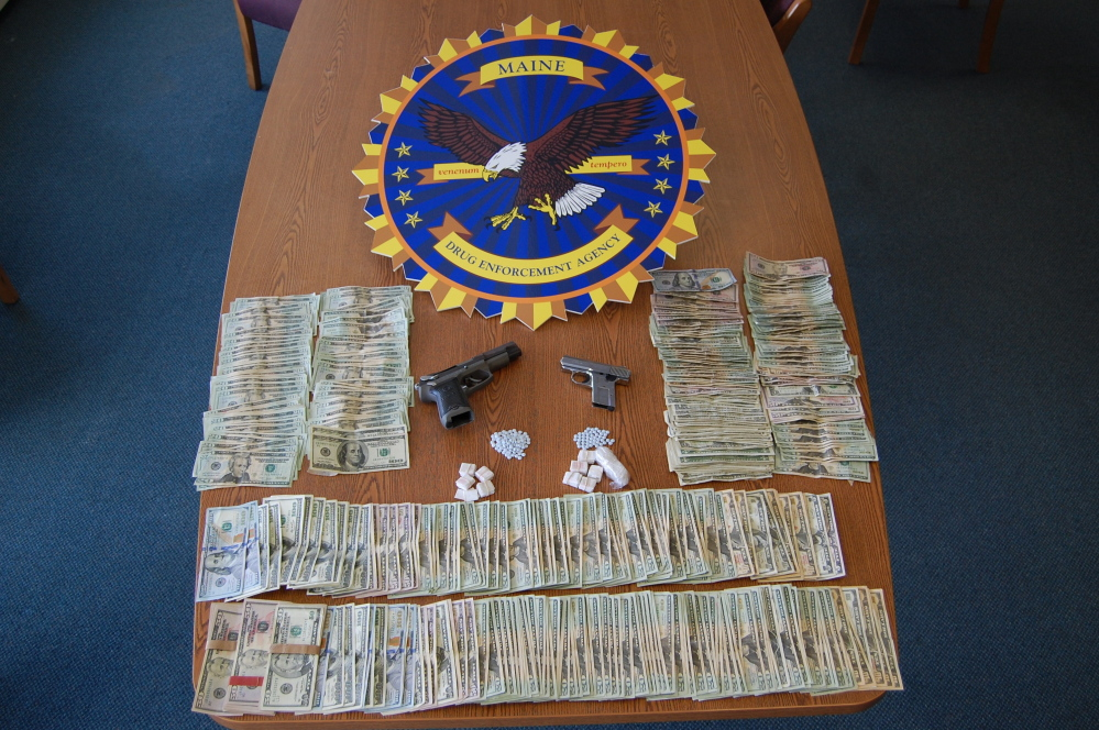 Police seized heroin, oxycodone and cash and guns in searches of houses in Bangor and Dedham.