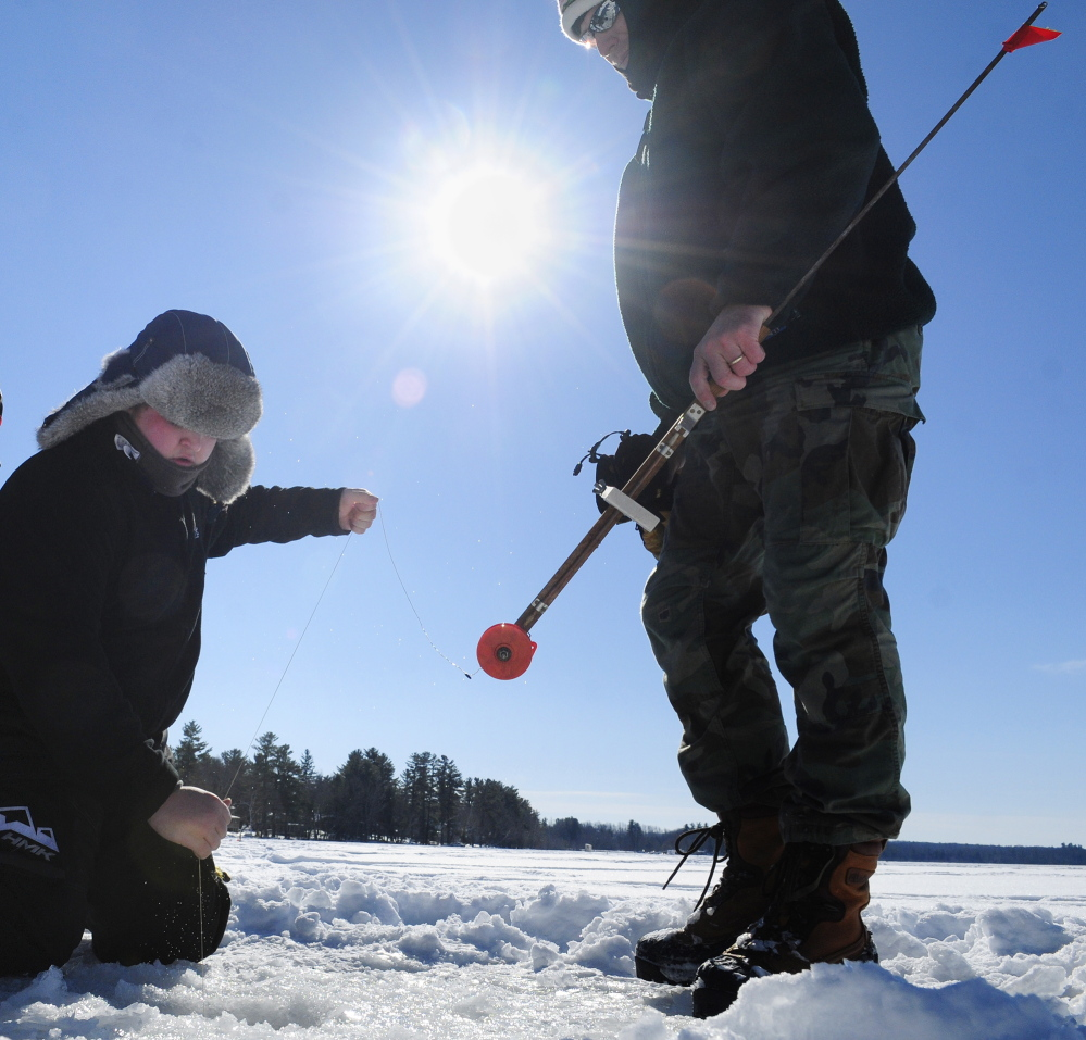 A FINE LINE: Collin Acord, left, pulls up a fish as Ron Emmons holds on to a trap Saturday during an RSU 2 fundraising ice fishing tournament at Cochnewagen Lake Town Landing in Monmouth.