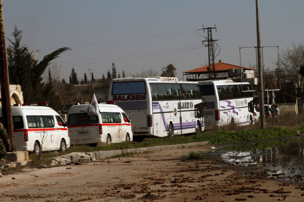 Some Syrian people on two buses followed by the Syrian Arab Red Crescent's vehicles evacuate Syria's battleground city of Homs, Friday.