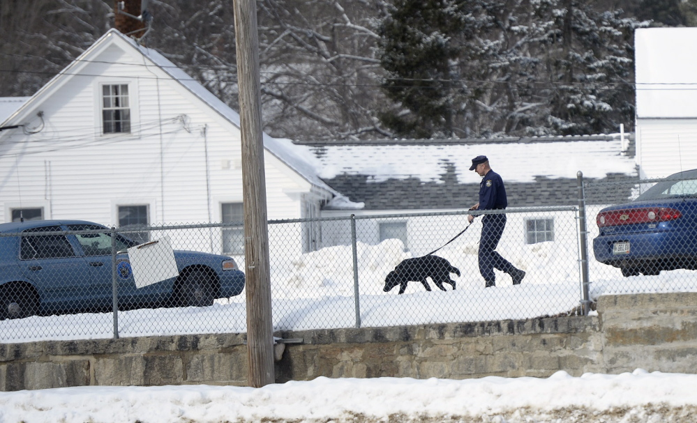 A Maine State Police trooper with a police dog makes his way across the parking lot of the York County Courthouse in Alfred on Monday. Court was canceled for the day after a bomb threat.
