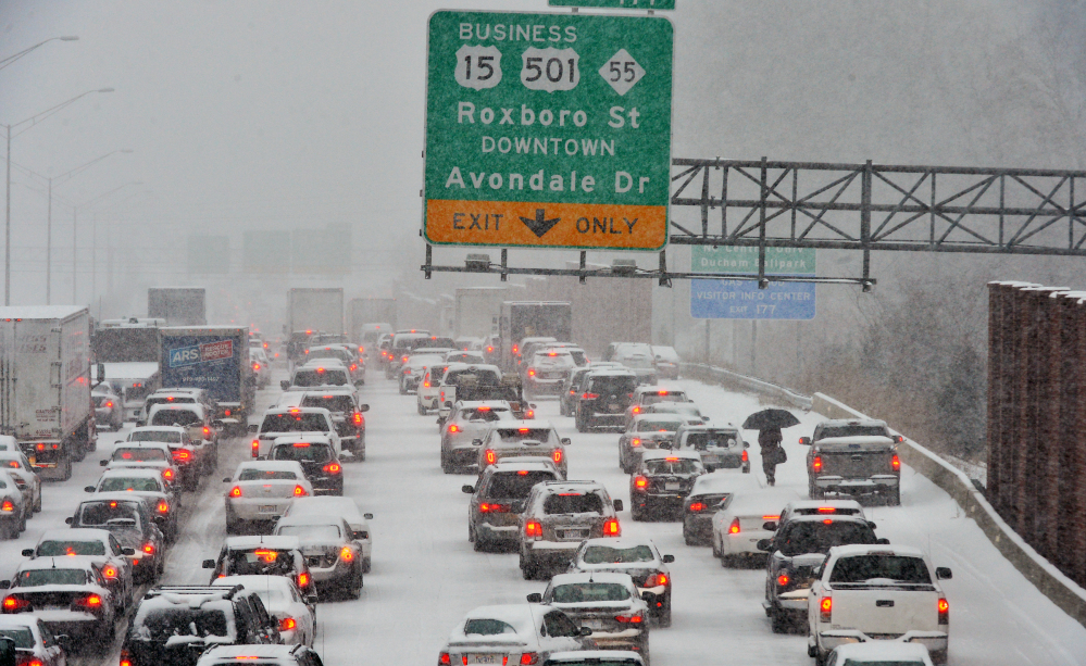 A motorist, right, who abandoned a vehicle, walks through stopped traffic on northbound Interstate 85 during a storm Wednesday in Durham, N.C.