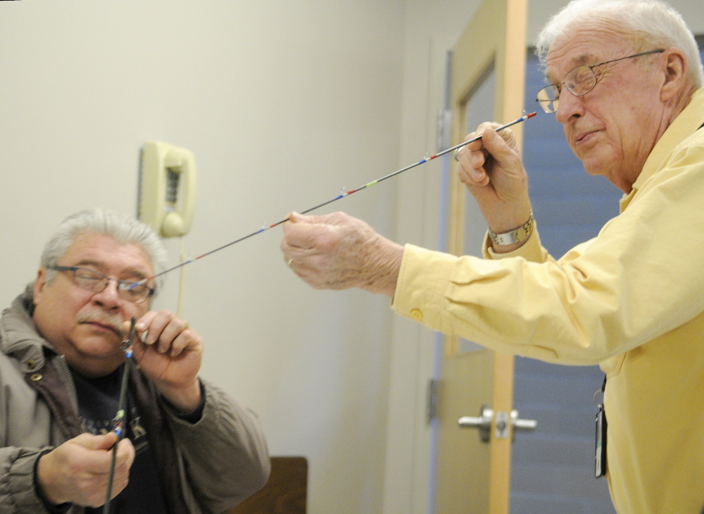 FLYING HIGH: Volunteer Don Taylor, right, inspects a section of a fly rod that veteran Dwaine LaChance assembled Wednesday at VA Maine Healthcare Systems-Togus during a meeting of Project Healing Waters. The group helps active and former service members experience fly fishing.