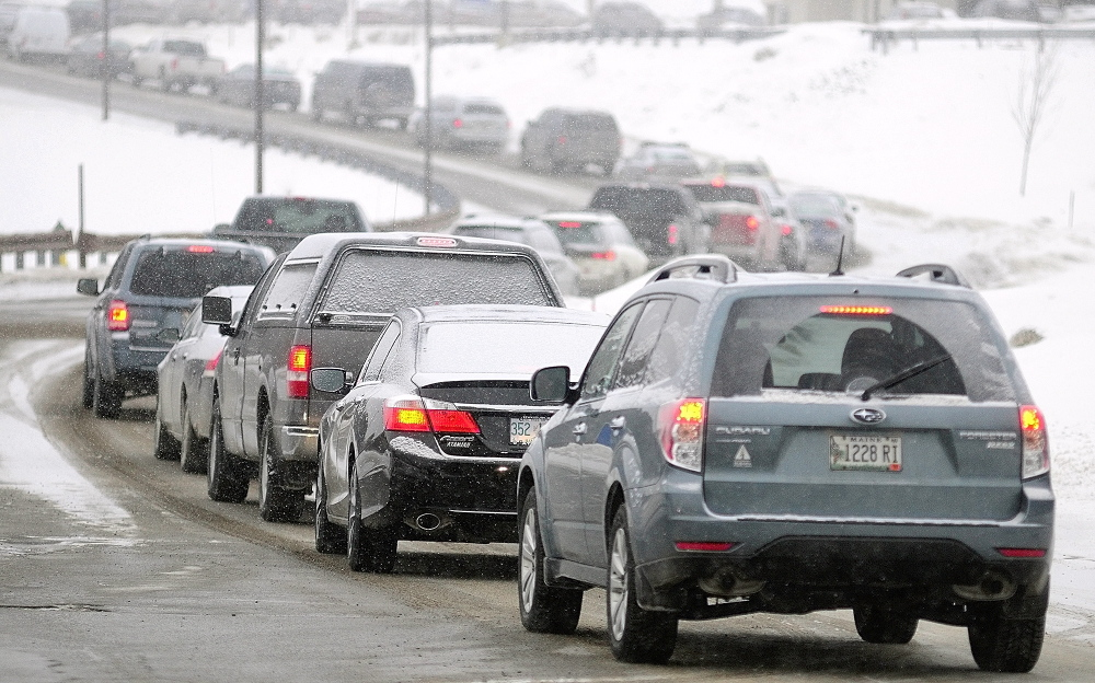SLOW GOING: A long line of cars heads down Commerce Drive toward Route 27 Thursday. There are several state government offices in the Central Maine Commerce Center and state workers in Kennebec and three other counties were let out of work early because of the snow storm.