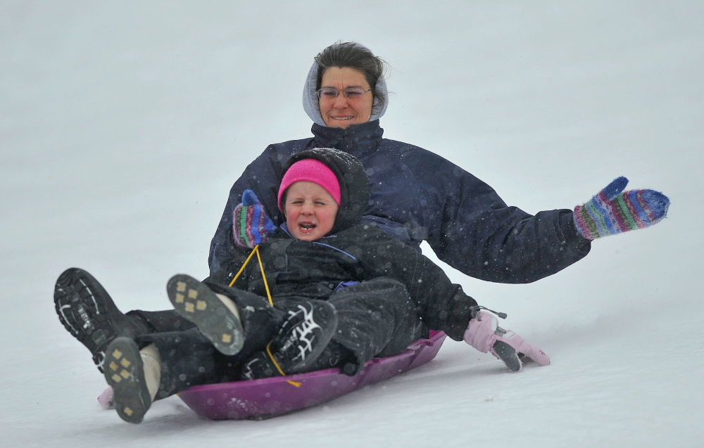 SLED HEADS: Karen Chase and Ysa Boothman, 7, cruise down the hill at Quarry Road Recreational Area in Waterville on Thursday as snow begins to fall.