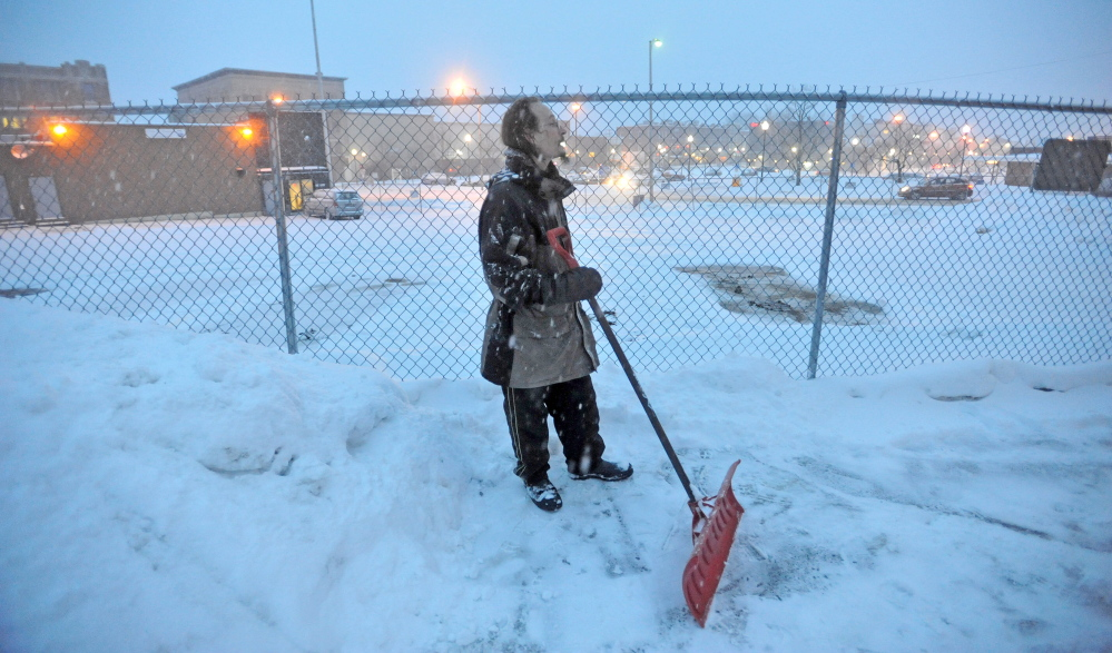 Staff photo by Michael G. Seamans STAYING AHEAD: Thomas Beeney takes a break after clearing the walkways at the Waterville Public Library as snow falls on Thursday. The winter storm is expecting to deposit at least one foot of fresh powder before moving out this afternoon.