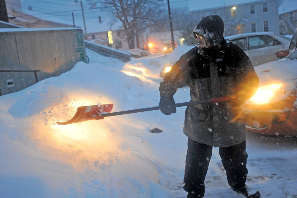 Staff photo by Michael G. Seamans STAYING AHEAD: Thomas Beeney clears the walkways at the Waterville Public Library as snow falls on Thursday. The winter storm is expecting to deposit at least one foot of fresh powder before moving out this afternoon.
