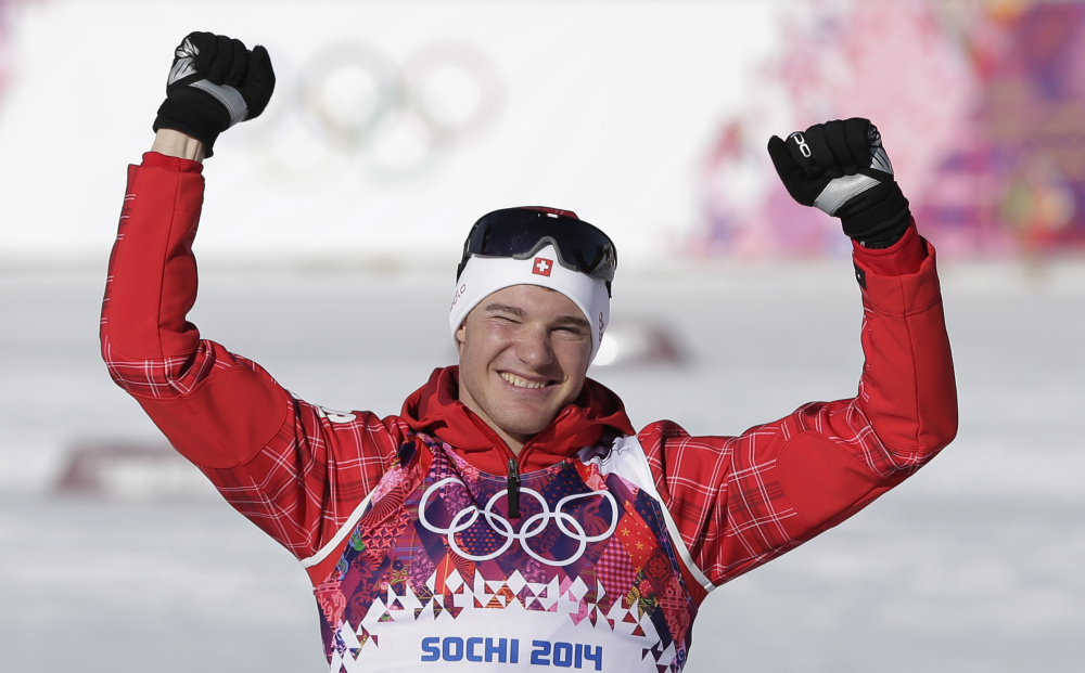 Switzerland's Dario Cologna celebrates winning the gold during the flower ceremony for the men's 15K classical-style cross-country race at the 2014 Winter Olympics Friday.