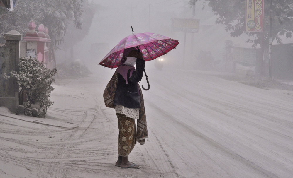 A woman walks on a road covered with volcanic ash in Yogyakarta, Indonesia, following an eruption of Mount Kelud Friday.