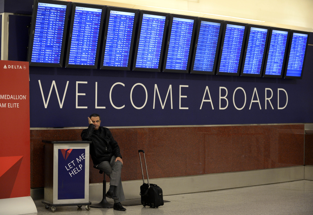 Airline passenger Hossam Shalaby of Egypt waits for his rescheduled flight to Orlando under the departure board showing hundreds of cancellations at Hartsfield-Jackson International Airport in Atlanta on Tuesday. The relentless snow and ice storms this winter have led to the highest number of flight cancellations in more than 25 years, according to an analysis by The Associated Press.