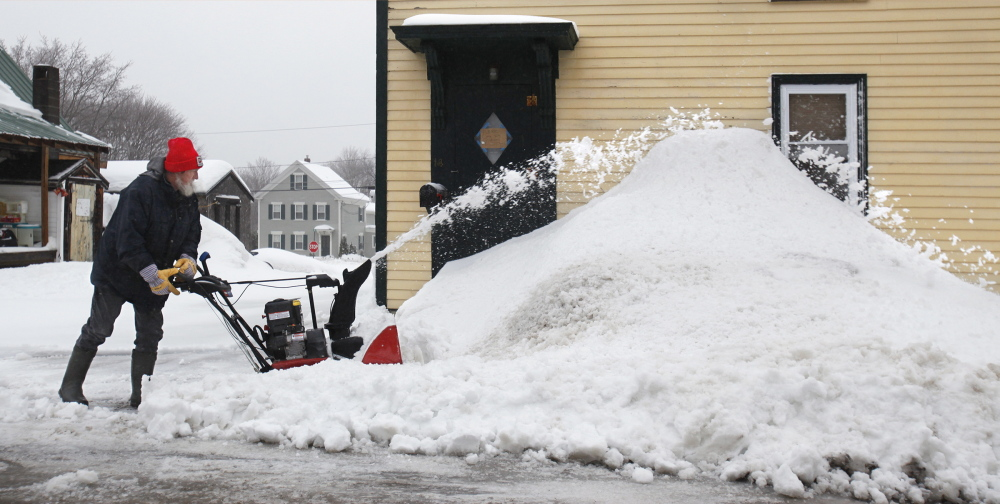 Ernest Brown clears waterlogged snow Friday from his driveway on Hovey Street in Kennebunk.