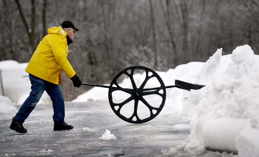 George Doody, 80, of Saco uses a Sno Wovel to clear snow from his driveway Friday. More snow is coming Saturday.