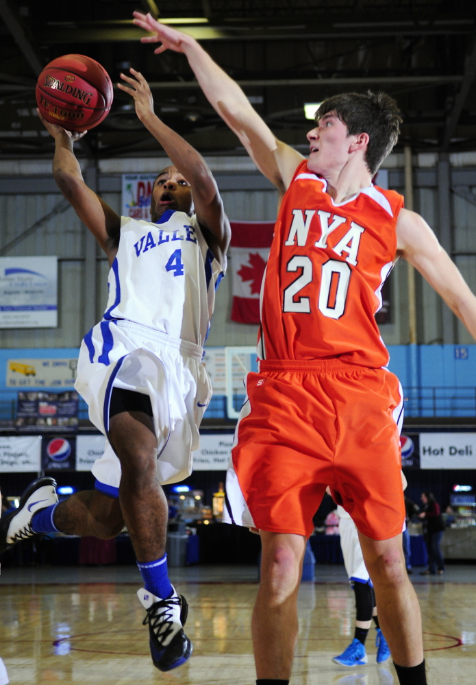 LAYUP: Valley guard Jordan Gillespie, left, goes for a shot past NYA forward Forrest Chicoine during a Western Maine Class D quaterfinal game Saturday at the Augusta Civic Center. The Cavaliers won 70-47.