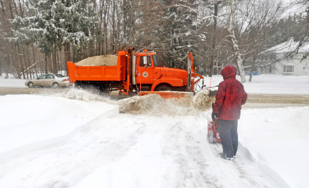 DIGGING OUT: Luke Violette, 17, watches as a plow pushes more snow onto his recently cleared driveway Friday on Mayflower Hill Drive in Waterville.