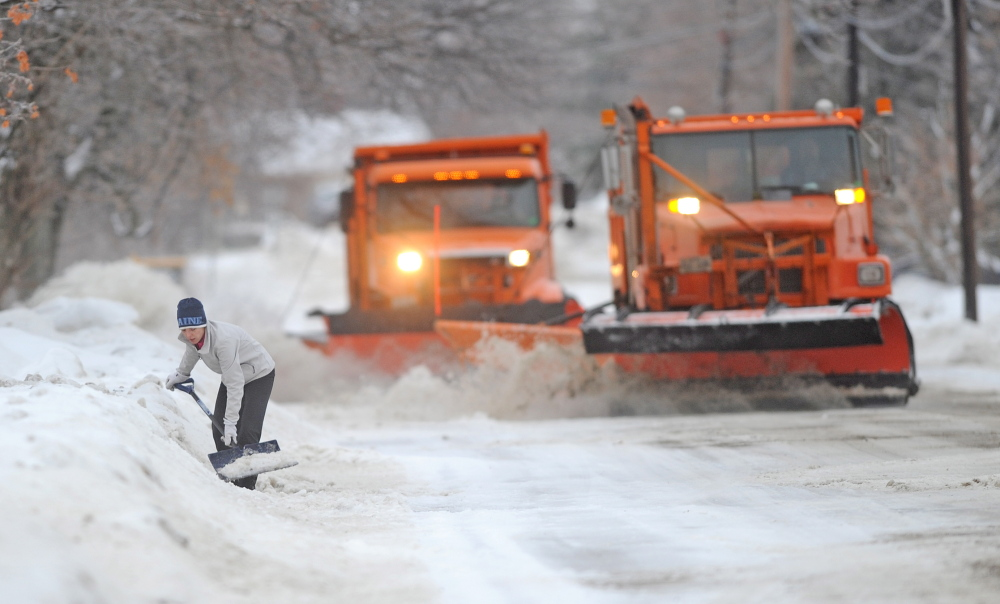 NEVERENDING JOB: Melinda Hansen tries to shovel her driveway on North Street in Waterville earlier this winter as two Waterville plow trucks bear down on her efforts..
