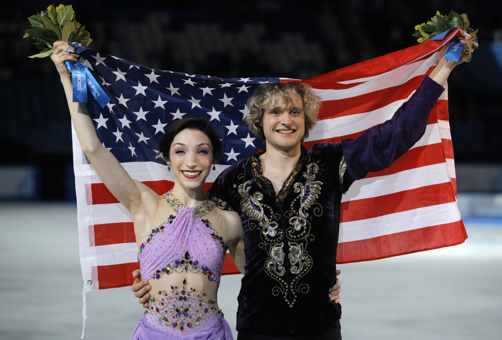 GOLD MEDAL: Meryl Davis and Charlie White of the United States pose for photographers after placing first in the ice dance free dance figure skating finals Monday at the Iceberg Skating Palace during the Winter Olympics in Sochi, Russia.