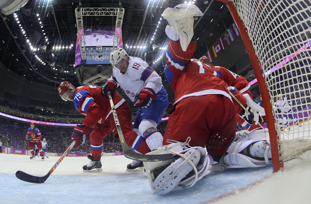 Russia goaltender Sergei Bobrovski clears the puck away from Norway forward Per-Age Skroder as Russia defenseman Andrei Markov helps defend in the third period of a men's ice hockey game at the 2014 Winter Olympics, Tuesday, Feb. 18, 2014, in Sochi, Russia. Russia won 4-0 to advance to the quarterfinals.