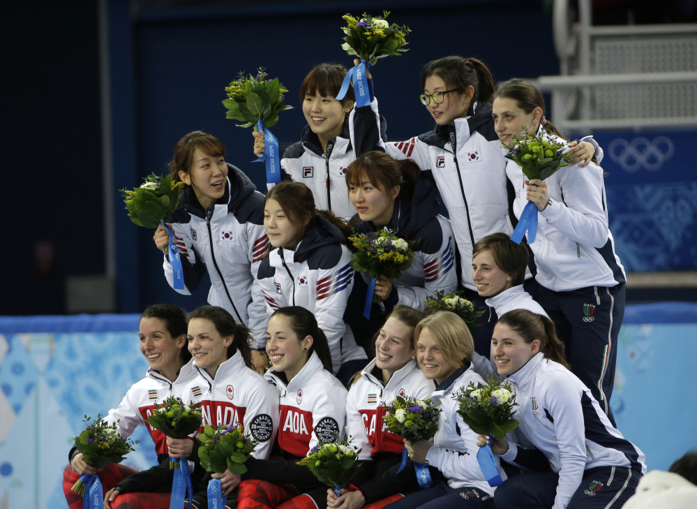 The South Korean team, top left, the Canadian team, front left, and the Italian team, top and bottom right, pose for photographers during the flower ceremony for the women's 3000m short track speedskating relay final at the Iceberg Skating Palace during the 2014 Winter Olympics, Tuesday, Feb. 18, 2014, in Sochi, Russia. South Korea placed first, followed by Canada and Italy.