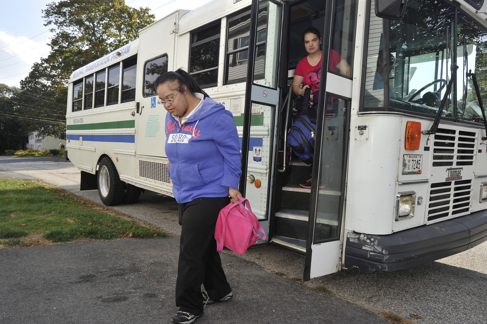 A bus arranged by Coordinated Transportation Solutions drops off Sheena Patel, who has Down syndrome, at her South Portland home last fall after her day at a sheltered work environment. After a flurry of amendments proposed by Democrats, the Legislature's Health and Human Services Committee voted to endorse a bill that would make changes to MaineCare's troubled rides system.
