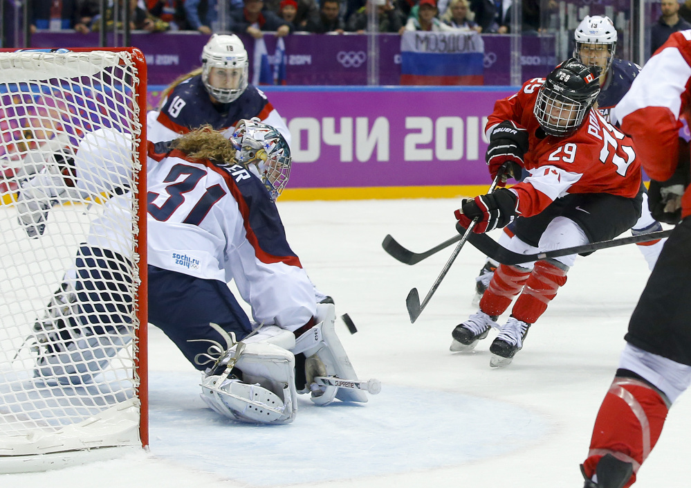 Marie-Philip Poulin of Canada (29) shoots to score the tying goal against USA goalkeeper Jessie Vetter (31) during the third period of the women's gold medal ice hockey game Thursday.