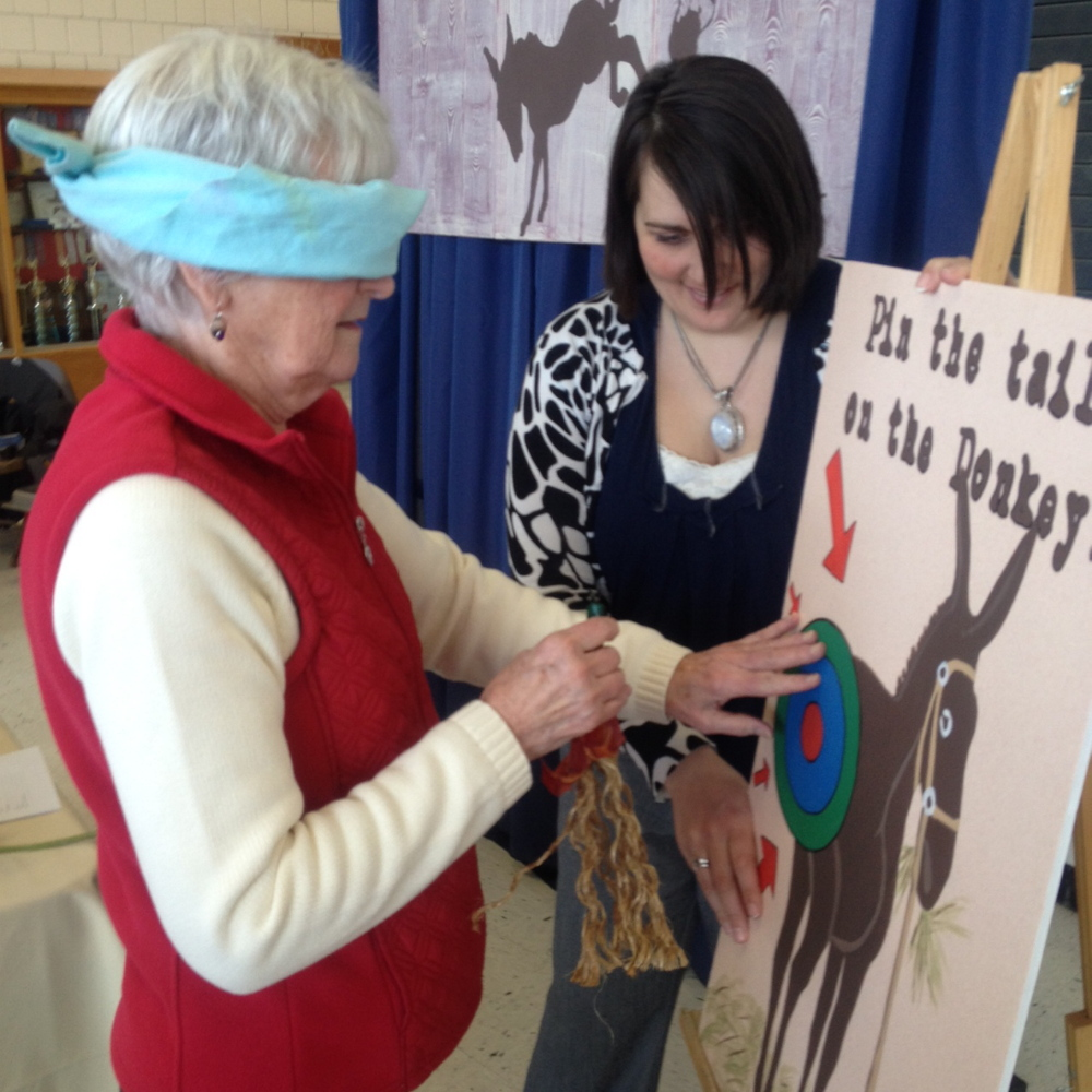 Fun at the Fair: Nancy Harrington, of Clinton, pins the tail on the donkey Saturday at Skowhegan's annual FAB Fair while Katie Quinn, owner of Ass Over Teakettle Bloody Mary Mix officiates. The winner of the game received a jar of the spicy mix.