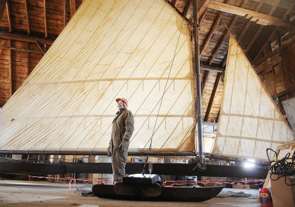 ICE RACER: Lloyd McCabe stands next to the ice boat that was re-assembled on the second floor of the carriage house at the Monmouth Museum. With a mast 25 feet high, McCabe and other volunteers worked for several months to put the craft together after being in storage 35 years.