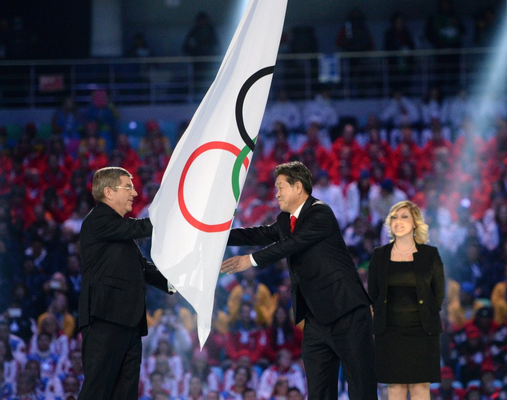 International Olympic Committee President Thomas Bach, left, hands the Olympic flag to Lee Seok-rai, mayor of Pyeongchang, during the closing ceremony of the 2014 Winter Olympics on Sunday in Sochi, Russia.
