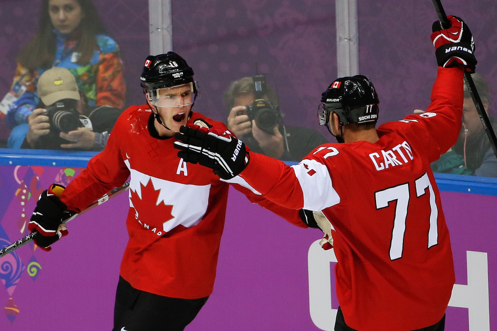 Jonathan Toews of Canada celebrates his goal with teammate Jeff Carter during the first period of the men's gold medal hockey game Sunday against Sweden at the 2014 Winter Olympics in Sochi, Russia