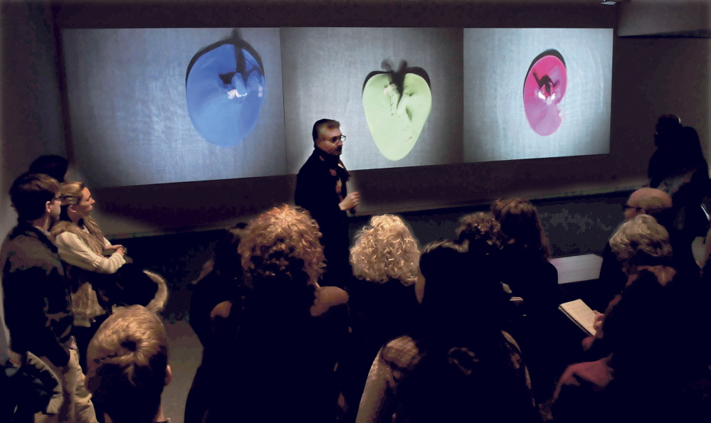 "DAZZLING: Ahmed Abdalla, artist and co-curator of the exhibit ""Histories of Now: Six Artists of Cairo,"" speaks in front of the video art installation titled ""Merge and Emerge"" of Egyptian dancers twirling in colorful garments at the Colby College Museum of Art in Waterville on Thursday."