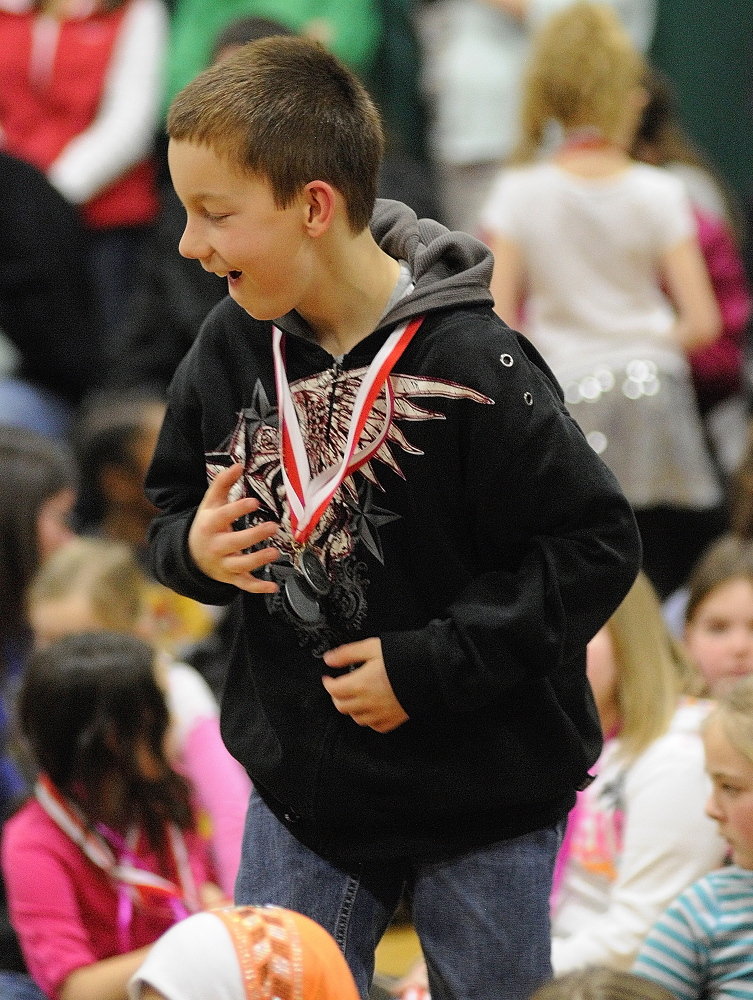 ACHIEVEMENT: Fifth-grader T.J. Jackson jumps up to get another one when his name is called for a third time during a medal ceremony for academic test scores on Thursday at Farrington School in Augusta.