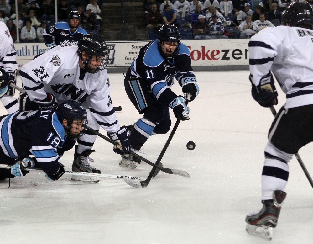 ONE LAST TIME: New Hampshire's Nick Sorkin (21) works to control a face off against Maine's Jon Swavely (18) and Steven Swavely (11) during the first period last season at the Whittemore Center in Durham, N.H. The brothers are hoping to extend their time together playing for the Black Bears.