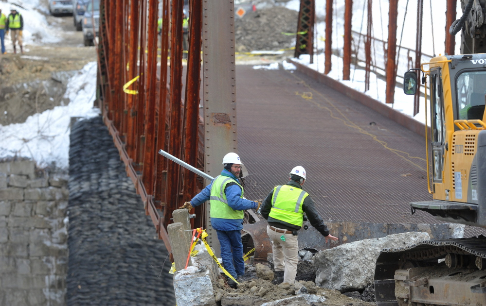 STANDING BY: Crews stand by as an excavator jackhammers the New Sharon bridge on Thursday.