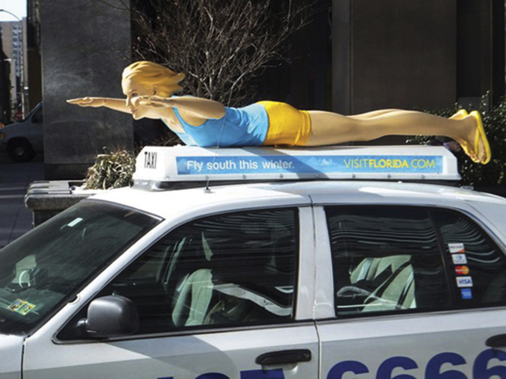 A fiberglass mannequin atop a taxi in Philadelphia promoting the warmth of Florida as winter rolls on in the northern parts of the country.