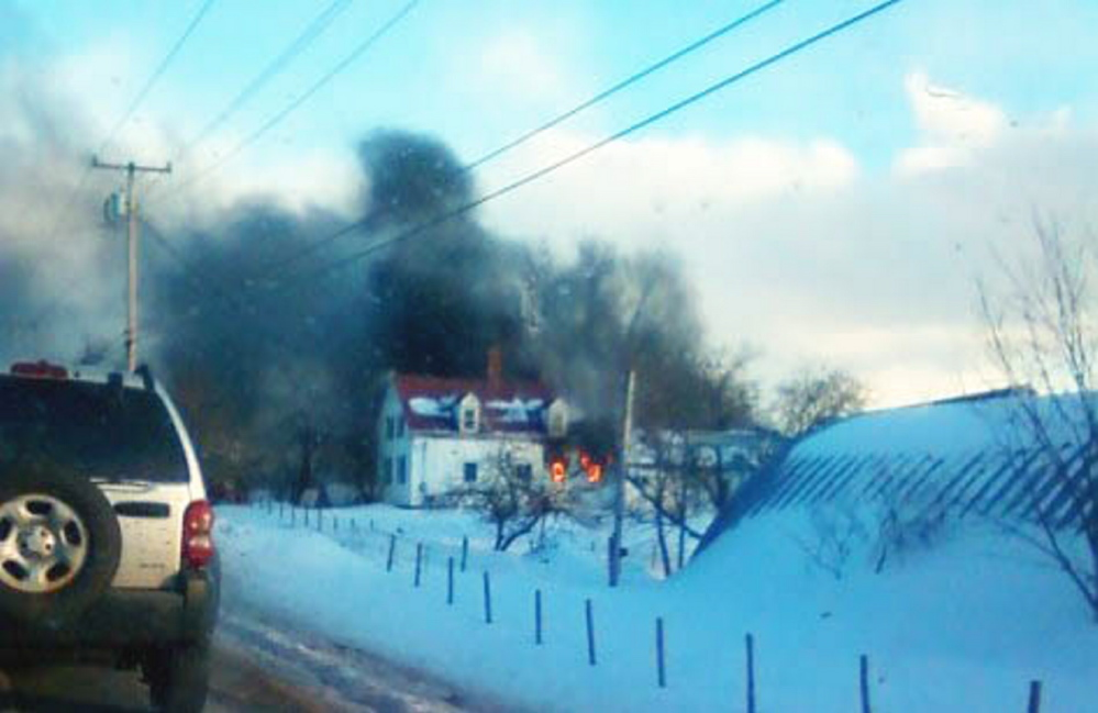 Flames are visible Wednesday as a farmhouse in Hollis burns. Three firefighters initially responded to the blaze.