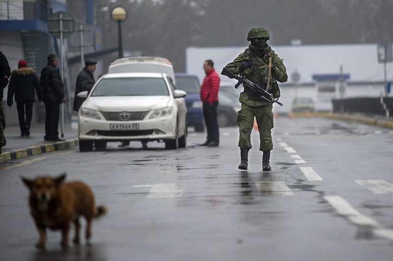 An unidentified armed man patrols a square in front of the airport in Simferopol, Ukraine, Friday, Feb. 28, 2014. Russian military were blocking the airport in the Black Sea port of Sevastopol in Crimea near the Russian naval base while unidentified men were patrolling another airport serving the regional capital, Ukraine's new Interior Minister Arsen Avakov said on Friday.