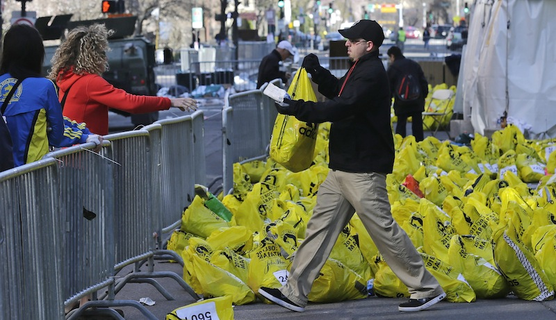 In this April 16, 2013 file photo, a worker returns a bag containing a runner's personal effects near the finish line of the Boston Marathon, after bombs placed in backpacks killed three people and inured more than 260 in Boston. This year's Boston Marathon will have a