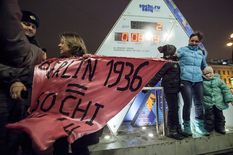 "A gay rights activist holds a banner in front of a large clock showing the number of days left until the start of the Olympic games as police officers approach, left, in St. Petersburg, Russia, Wednesday, Feb. 5, 2014. Russian gay rights activists protested the upcoming Olympic Games in Sochi. Two activists unfurled banners reading ""Berlin 1936 = Sochi 2014,"" referring to the Olympic Games that were held in the capital of Nazi Germany. One-man pickets are legal in Russia and the two activists holding signs were spaced far enough apart that neither was arrested."