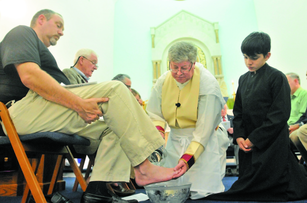 Priest: The Rev. Larry Jensen, center, washes the feet of parishioner David Lee, left, in 2013 as server Ben Hodgkin, right, watches the Holy Thursday ritual at St. Joseph Maronite Church in Waterville.