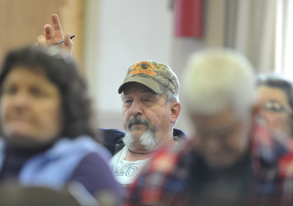 Residents Ask questions: Carroll Gould, raises his hand to ask a question during the annual Town Meeting at the Cornville Town Hall on Saturday.