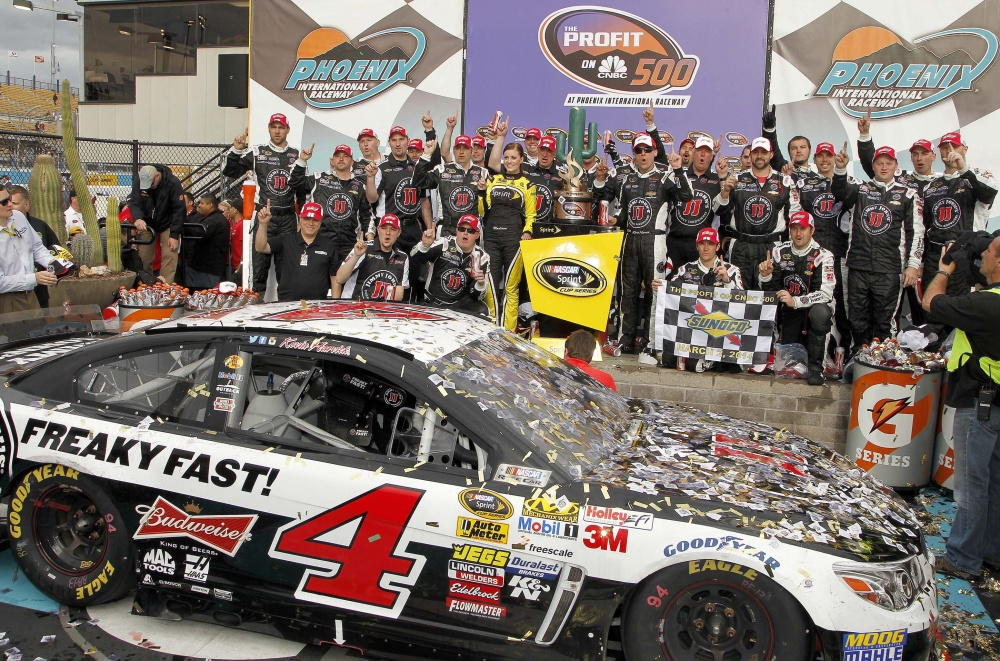 WINNER, WINNER: Kevin Harvick, standing to the right of the winner's trophy, joins his crew in posing for photographers in Victory Lane after winning The Profit on CNBC race Sunday in Avondale, Ariz.