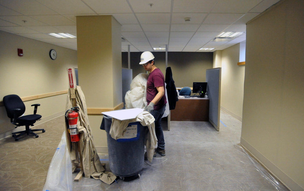 HOSPITAL WORK: Nate DeLeon, a laborer with JF Scott Construction, clears a portion of the newly renovated patient check-in office at Thayer Center for Health in Waterville on Feb. 21, 2014. The hospital is undergoing a $16 million renovation to be completed by Oct. 1, 2014.