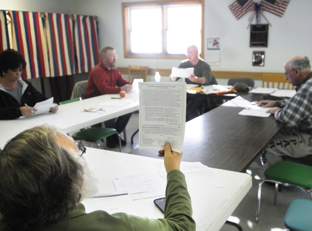 PARTY CAUCUS: James Hynson inspects a document Sunday during the Democratic Party caucus in Pittston. Democrats met across the state to elect officers and prepare for the fall election cycle.