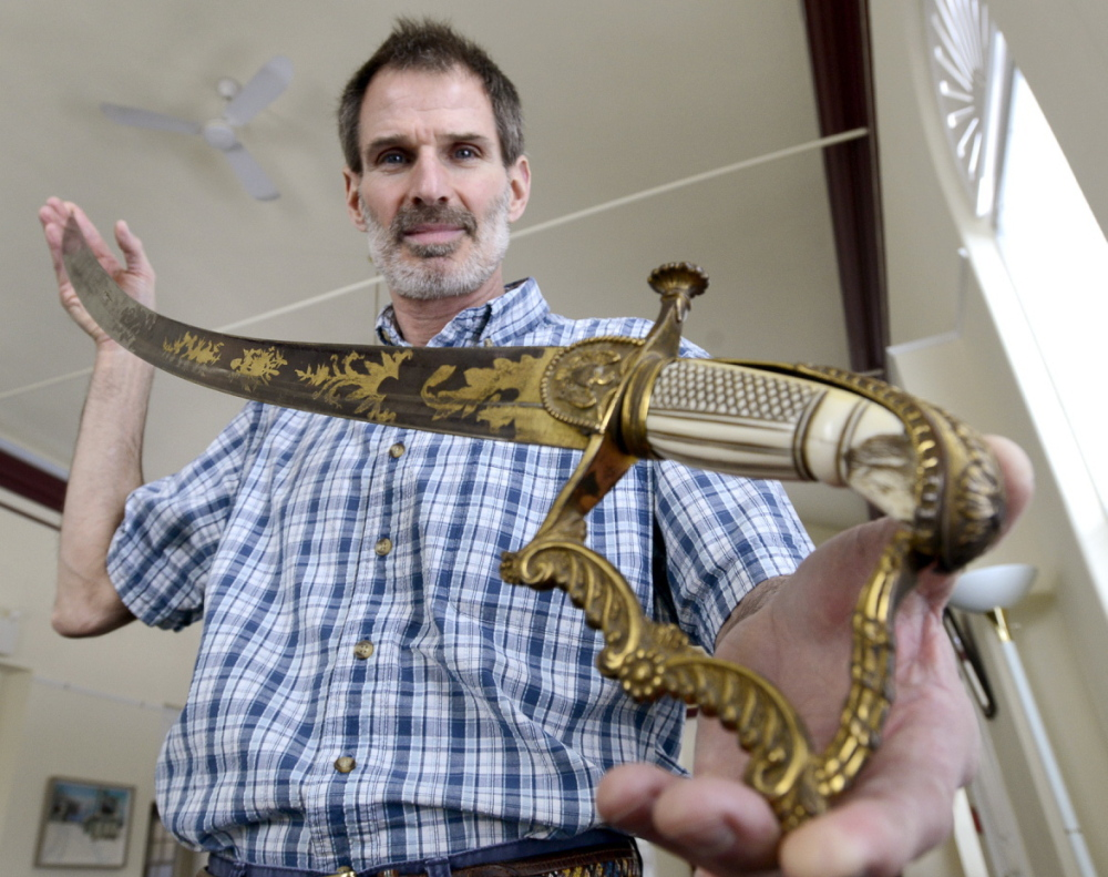 Thomas Bennett, director of Prince Memorial Library, displays a sword possibly owned by President Andrew Jackson.