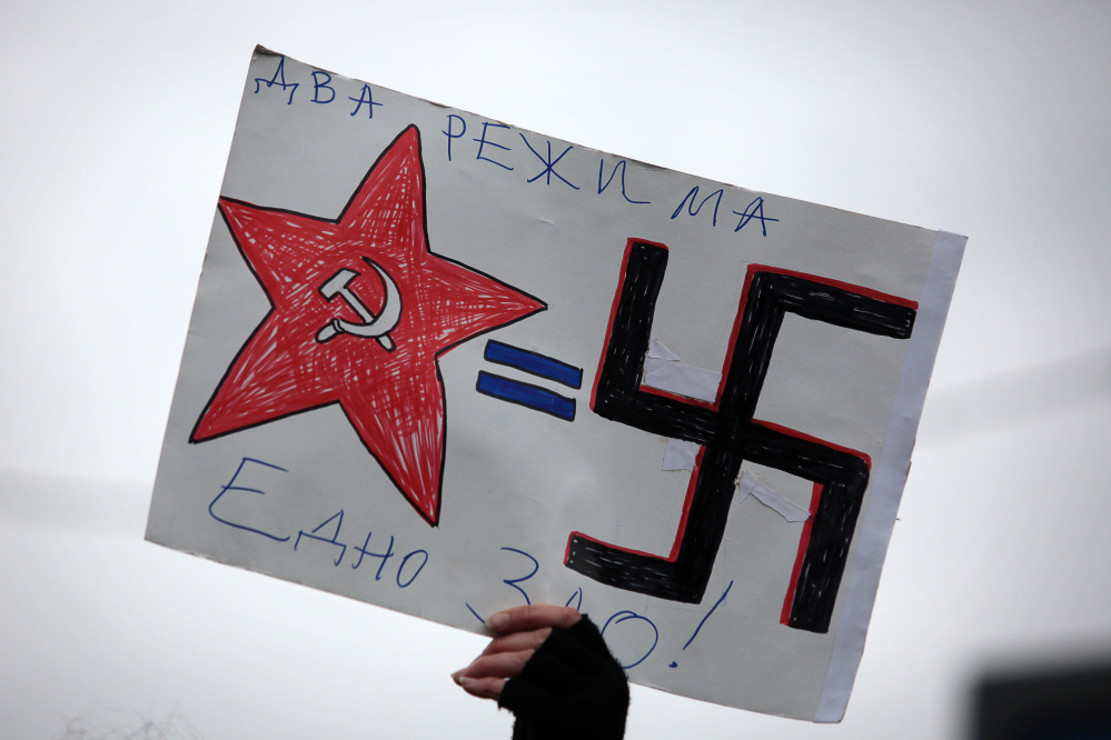 "A Bulgarian protester holds a poster depicting Soviet-era Russian and Nazi symbols reading in Bulgarian ""Two regimes, but one evil"" during a protest in front of the Russian embassy in Sofia, Monday. Demonstrators condemned Russian military actions in Ukraine."