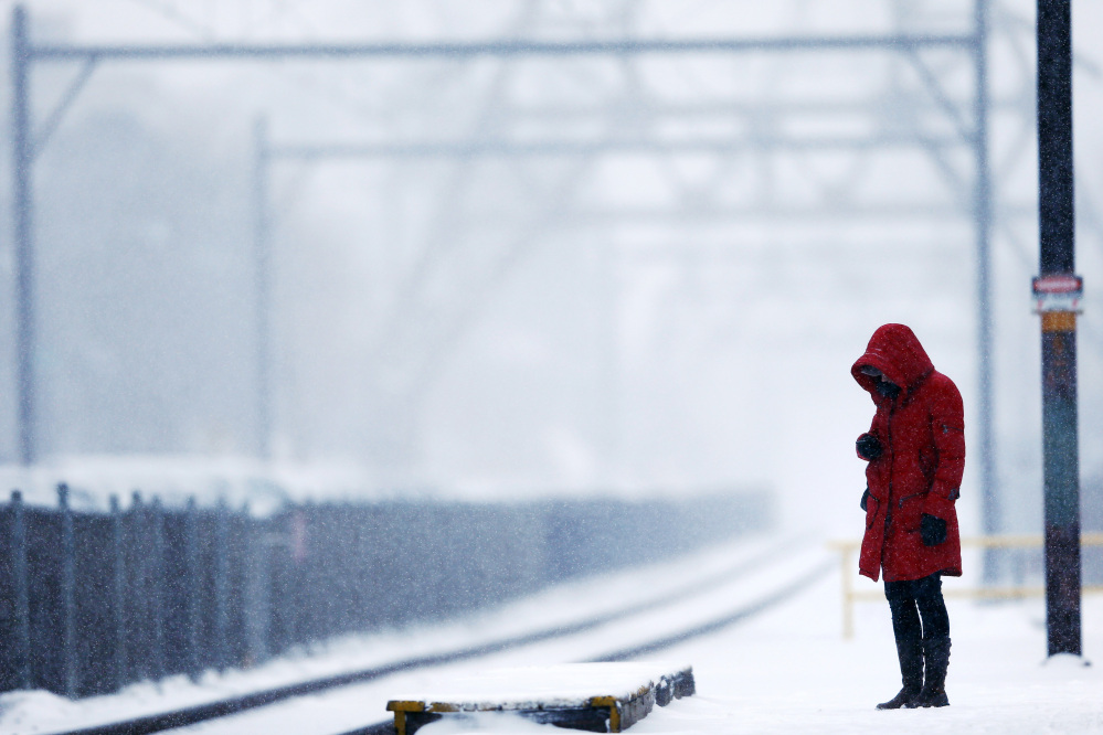 A morning commuter waits on a train during a winter snowstorm Monday, March 3, 2014, in Philadelphia.