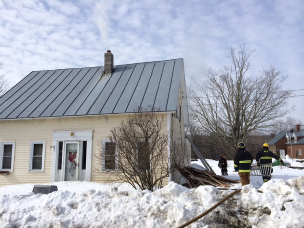 HOUSE DAMAGED: Firefighters work at the scene of a fire Wednesday morning at 17 School St. in Athens.