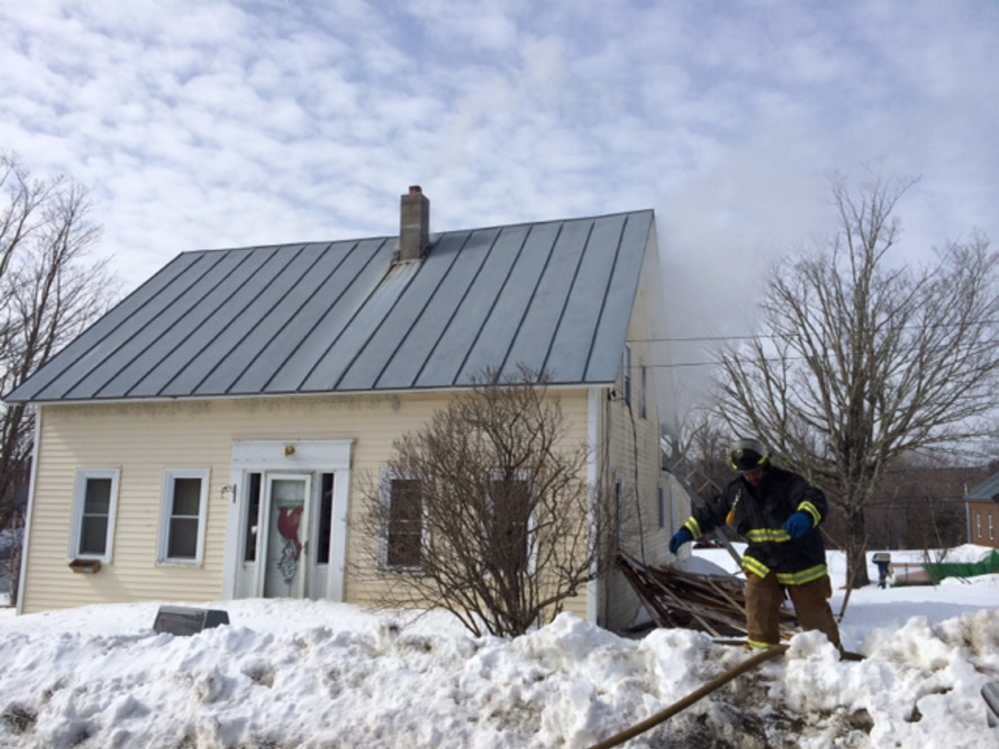 HOUSE DAMAGED: A firefighter works at the scene of a fire Wednesday morning at 17 School St. in Athens.