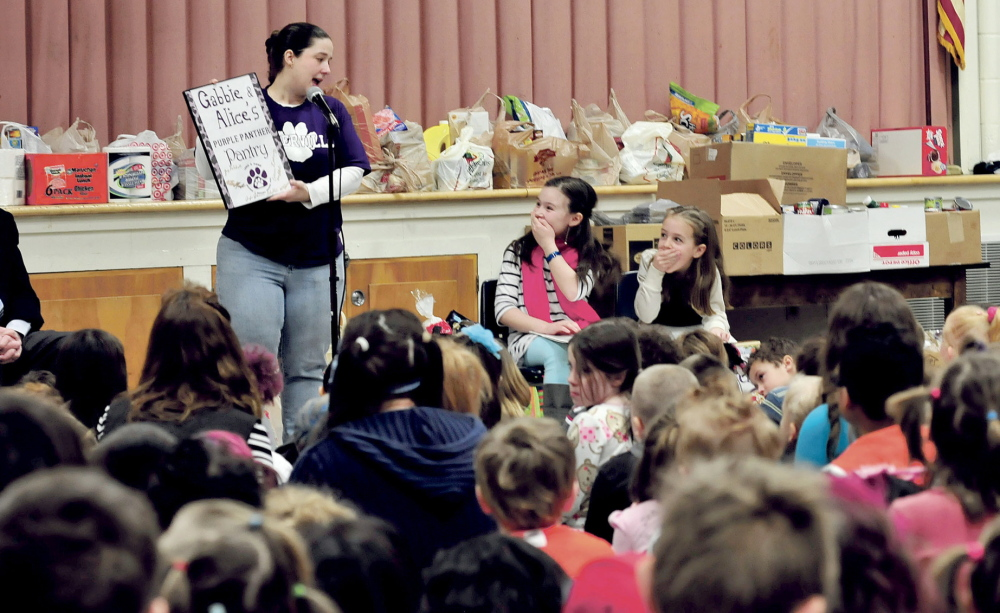 EARLY DISTINCTION: George J. Mitchell School students Gabbie St. Peter, left, and Alice Willette react happily Wednesday after school PTO President Jennifer Johnson announced that the school food pantry has been named Purple Panther Pantry in recognition of the girls' efforts.