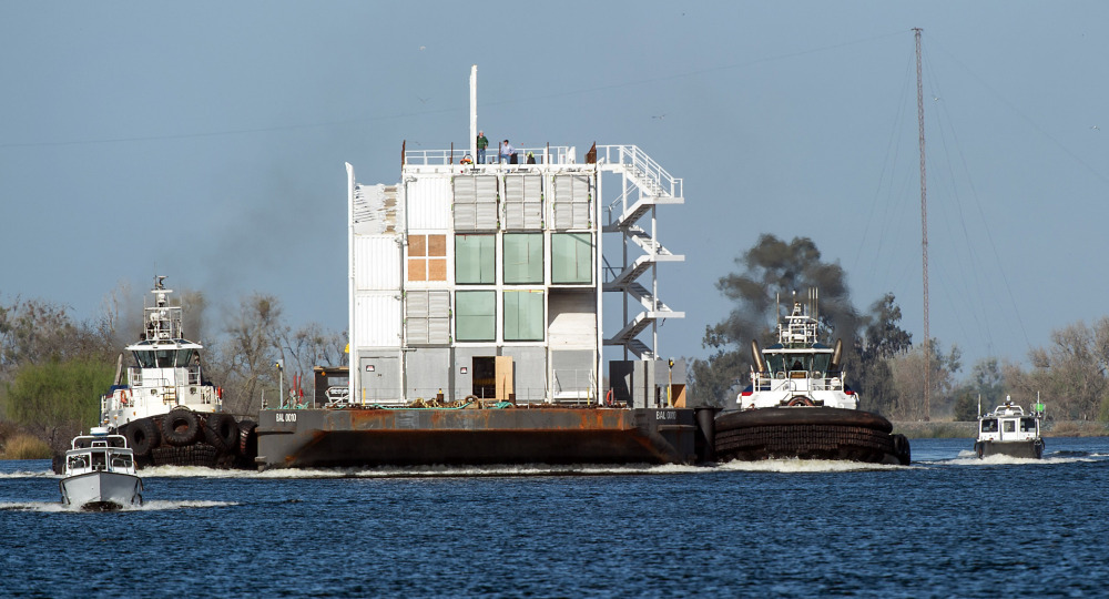 The Google mystery barge is guided through a channel on its way to the Port of Stockton in California on Thursday. The Internet company was ordered to move it out of San Francisco because it lacked the proper construction permits. A second mystery barge, berthed in Portland Harbor, doesn't have any permit issues.